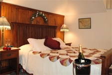 Curtis Michigan Accommodations - Step inside this premier Lakeside Country Inn and enjoy the warmth of the ten-foot stone fireplace. Wander up the beautiful open stairway to where eleven distinctive guest rooms await you. Each room is uniquely decorated in turn of the century decor with warm chenille spreads, country quilts, gracious antiques, beautiful photos, prints and comfy throw rugs under foot. Relax and settle right into comfort.